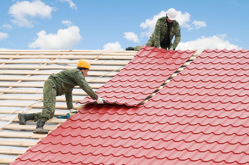 Stavaři pokrývají střechu